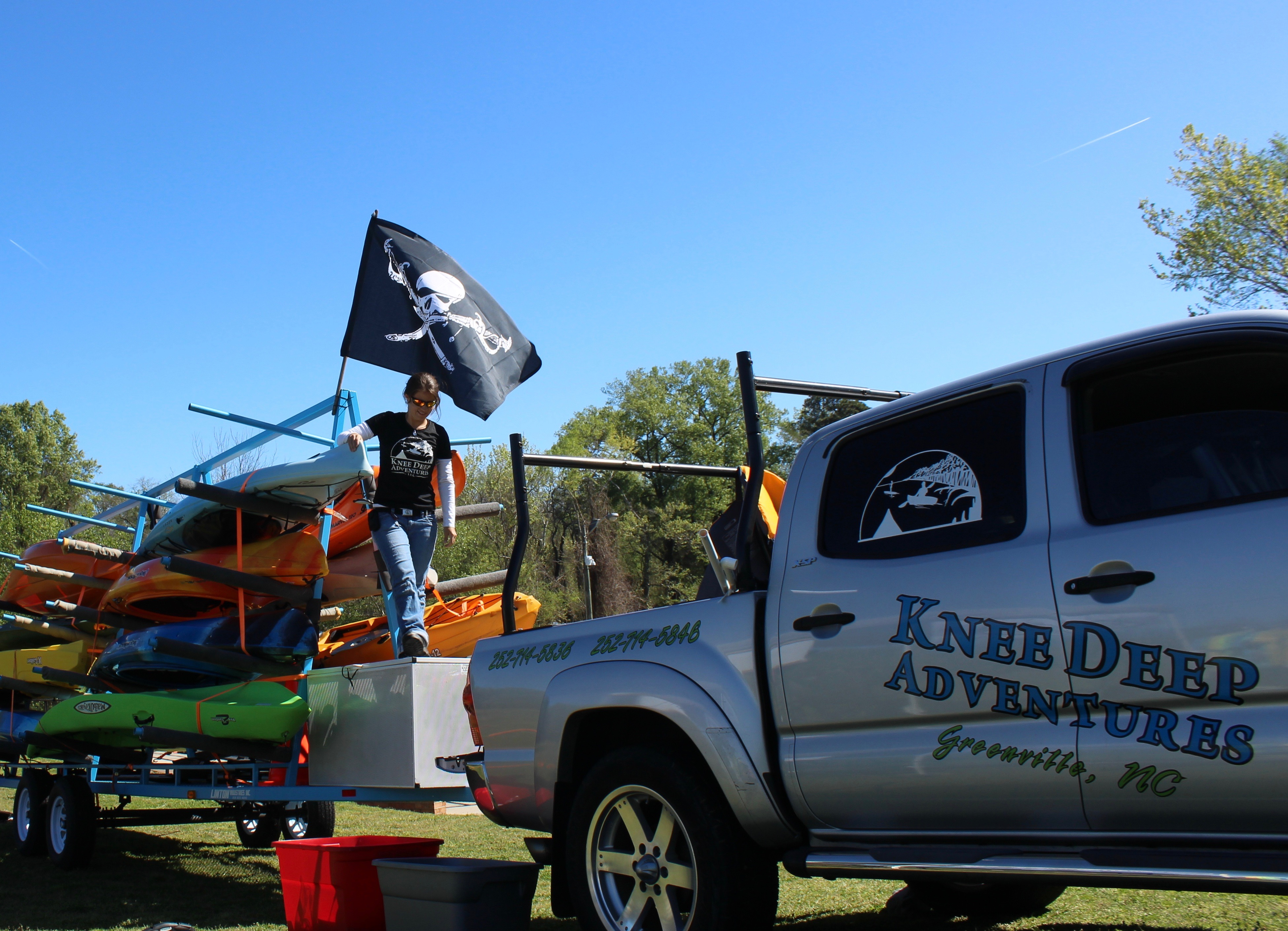 image shows Kelsey Curtis of Knee Deep Adventures in Greenville NC with kayaks and company truck